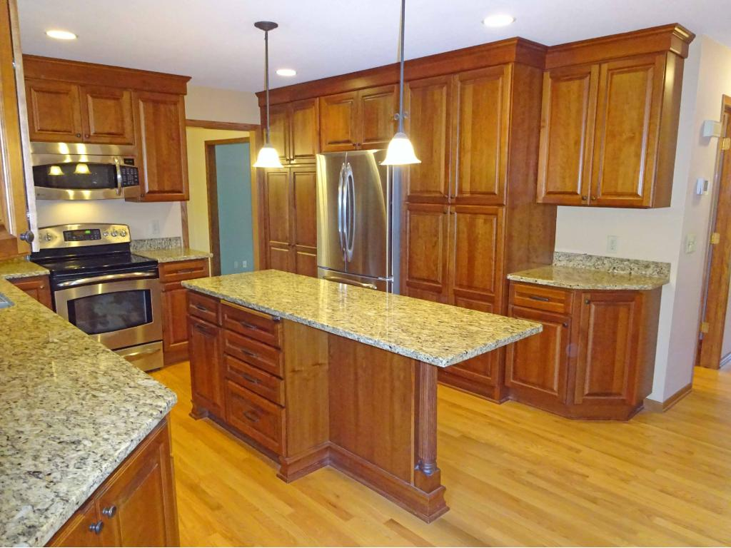 Spacious granite center island with cabinet cut in for bar stools.