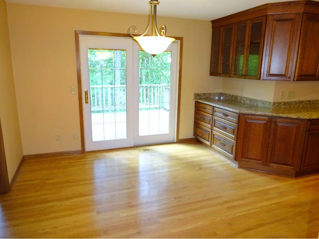Main floor family room with large stone fireplace and large flanking windows overlooking the woods and pond.