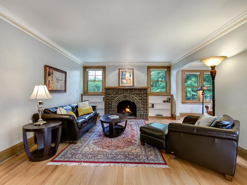 Large living room with beautiful hardwood floors and hand painted crown molding. Enjoy winters by sitting next to the wood burning fire place.
