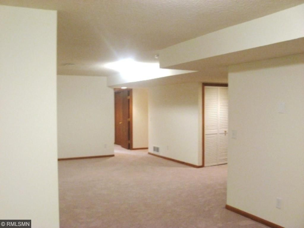 Basement with another bedroom with new carpet paint ceiling fan and egress window