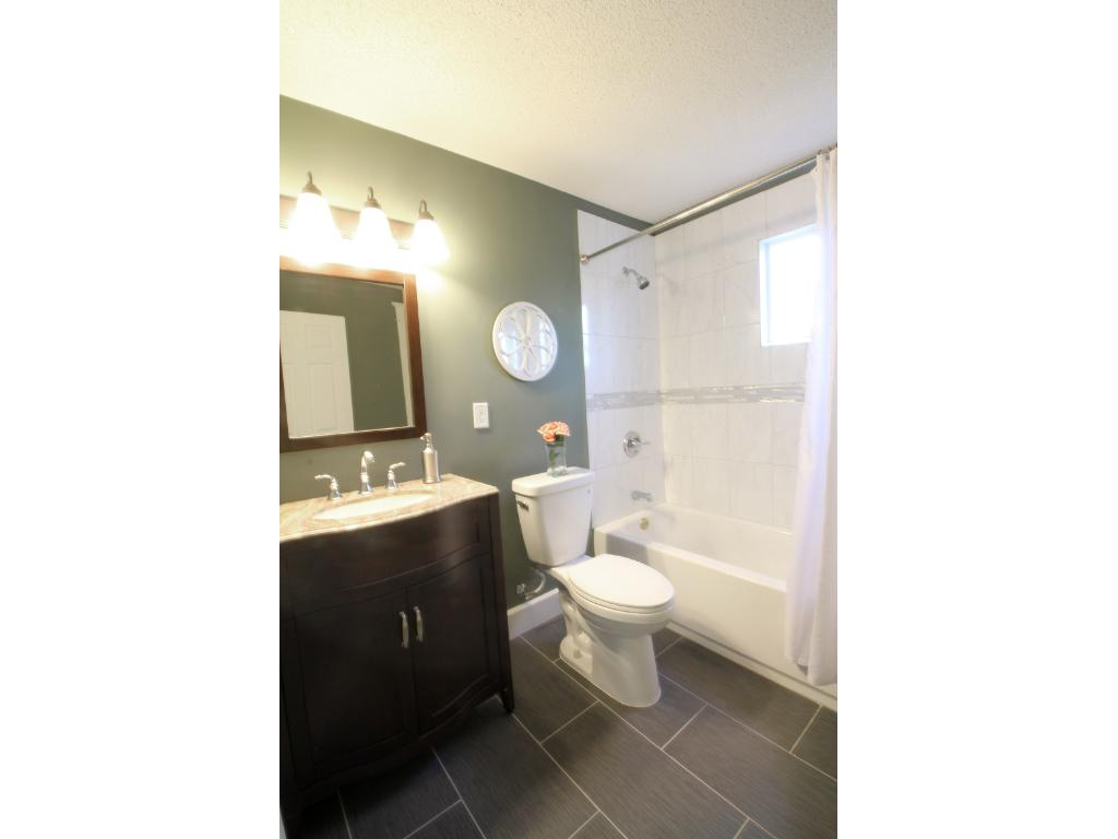 Remodeled from top to bottom - tile, paint, tub, vanity, lighting, paint....nice size bathroom.