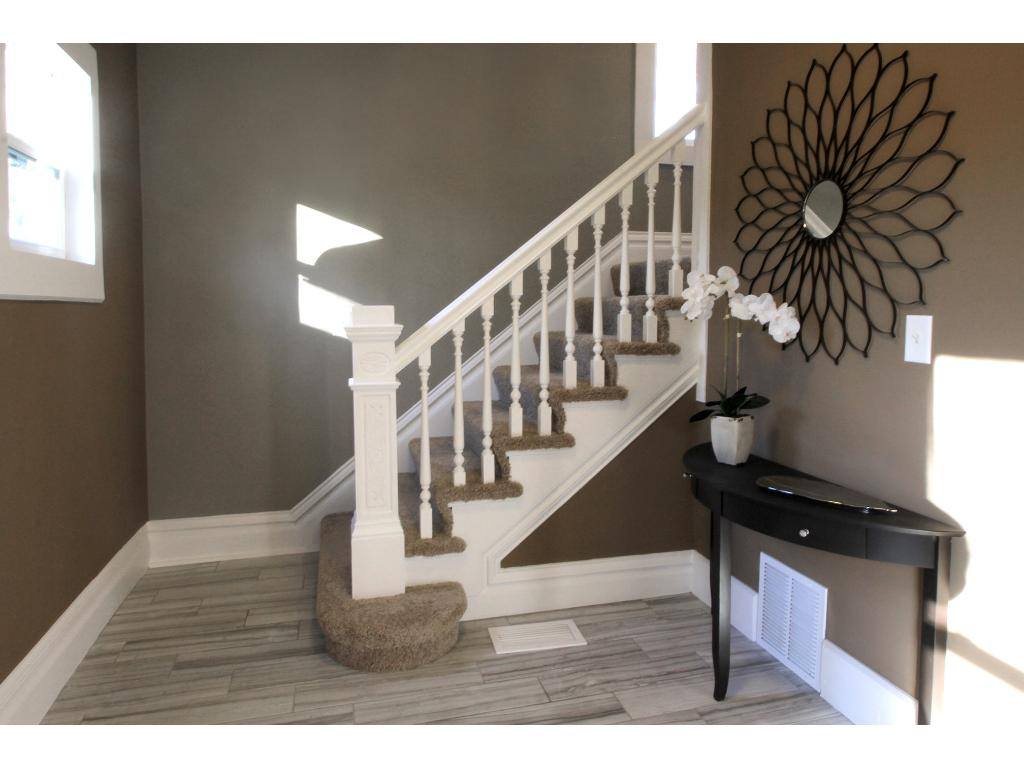 Stairs leading to upper level with 3 bedrooms and full bathroom.