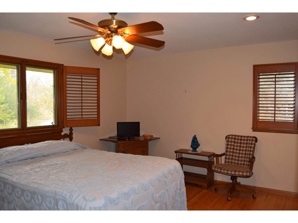 Master bedroom has two windows, recessed lighting, fan/light fixture, hardwood floor, and an attached bath.