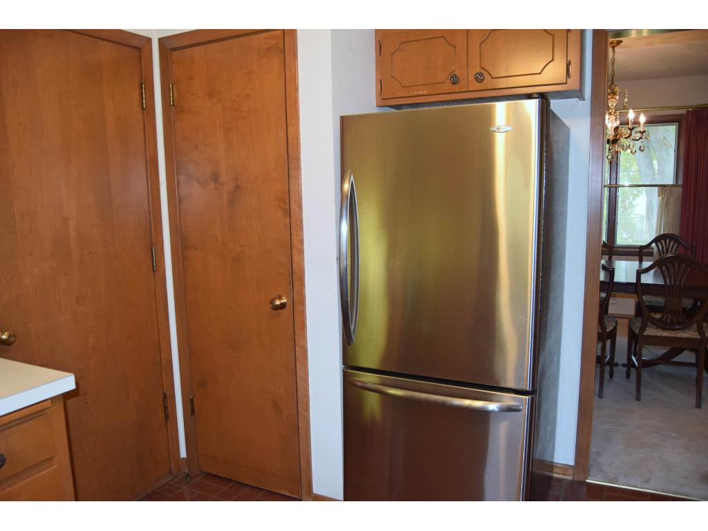 Refrigerator and pantry cupboard are within easy reach. Note the newer stainless steel appliances.