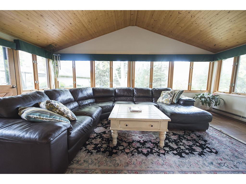 Large, open, bright and comfortable 4 season porch with in floor heat and great panoramic views!  Notice the custom wood ceiling:)