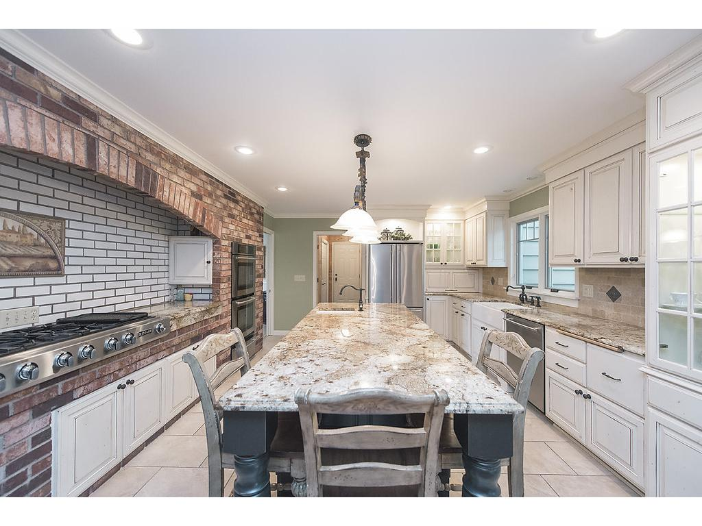 Beautiful kitchen - 60K remodel with tons of storage, granite countertops, top of the line appliances, brick, white cabinetry, tiled floors and so much more - truly breathtaking!