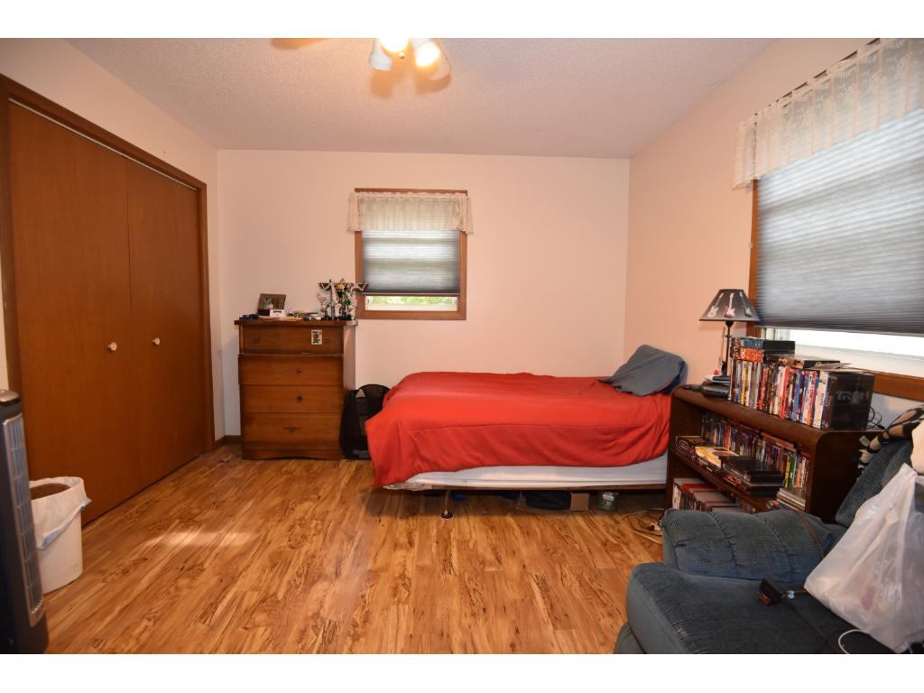 Conforming bedroom featuring lots of space and nicely refinished pine floors.