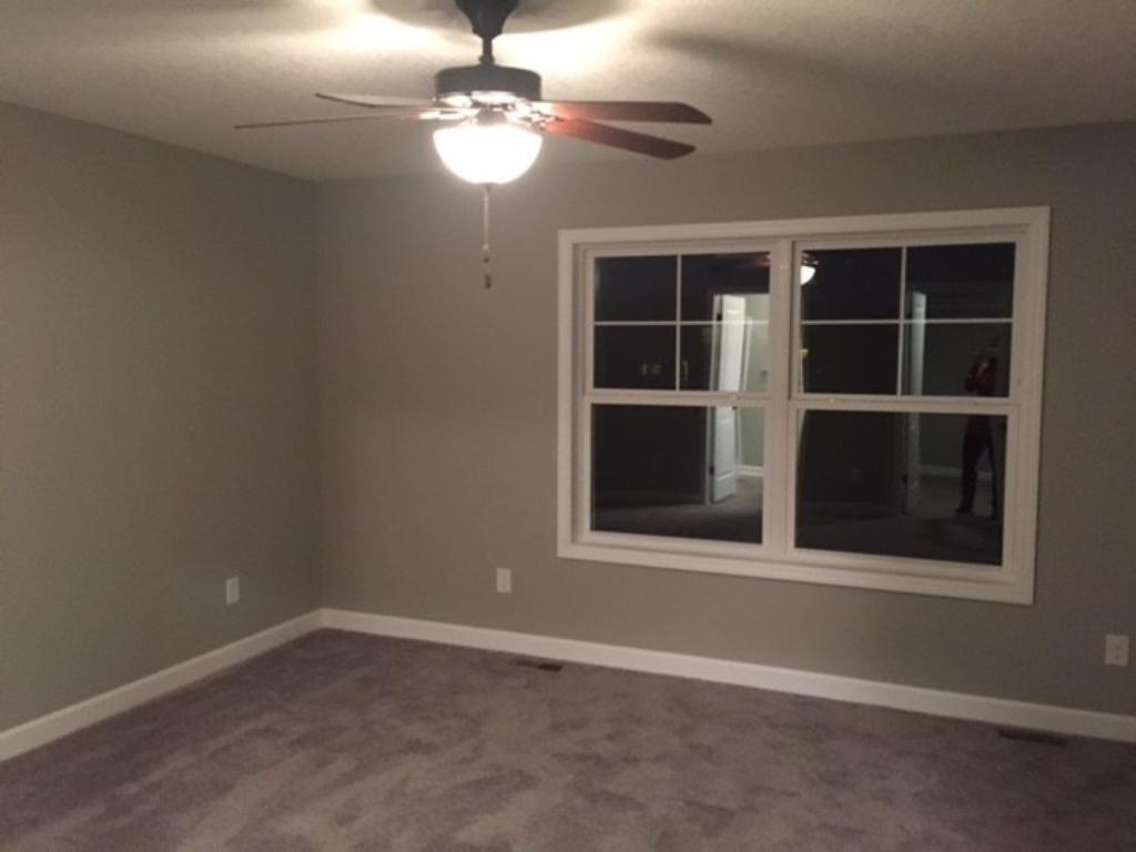 Master bedroom with large windows and ceiling light