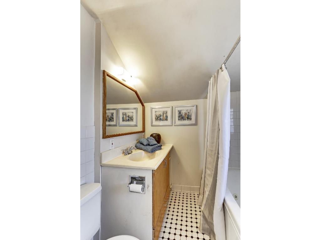 Upper level master has the classic black and white tiles as in the main floor bath. For a more current look, the cabinets and mirror fram could be painted white. Just a suggestion.
