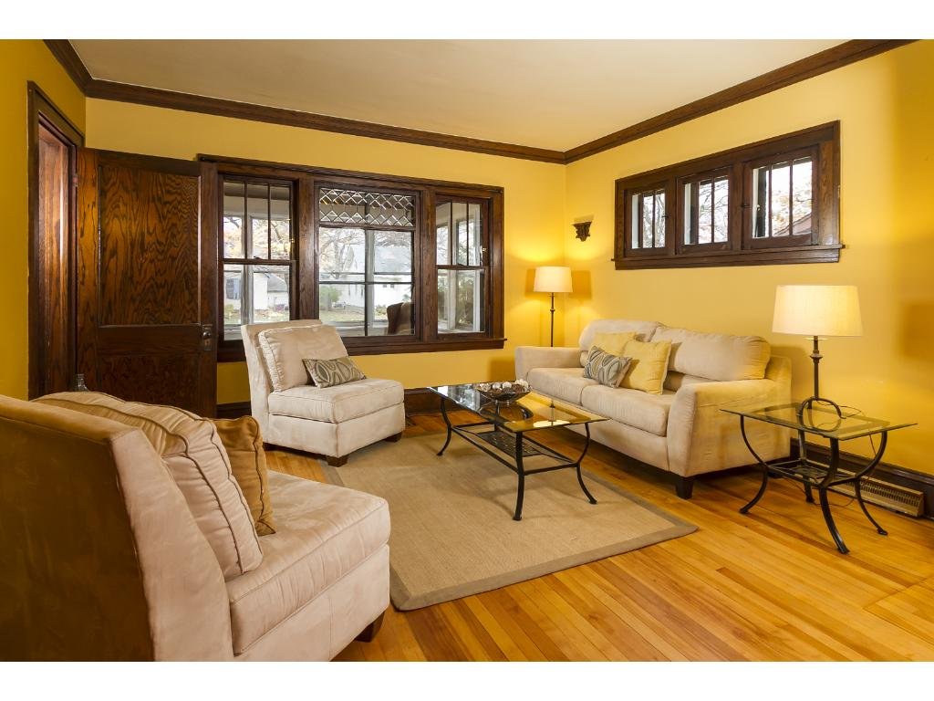 Living room, with gleaming hardwood floors, original woodwork and leaded glass window.