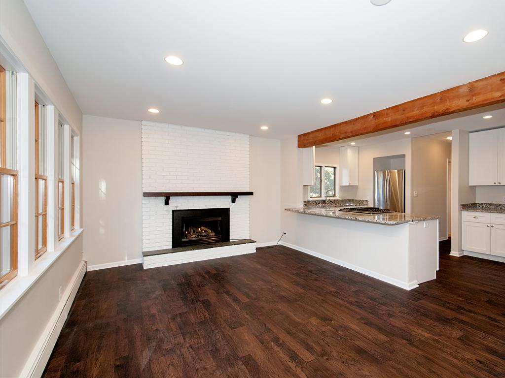 Gas fireplace highlights this living room / dining room space. A wall of windows bring in so much natural light.