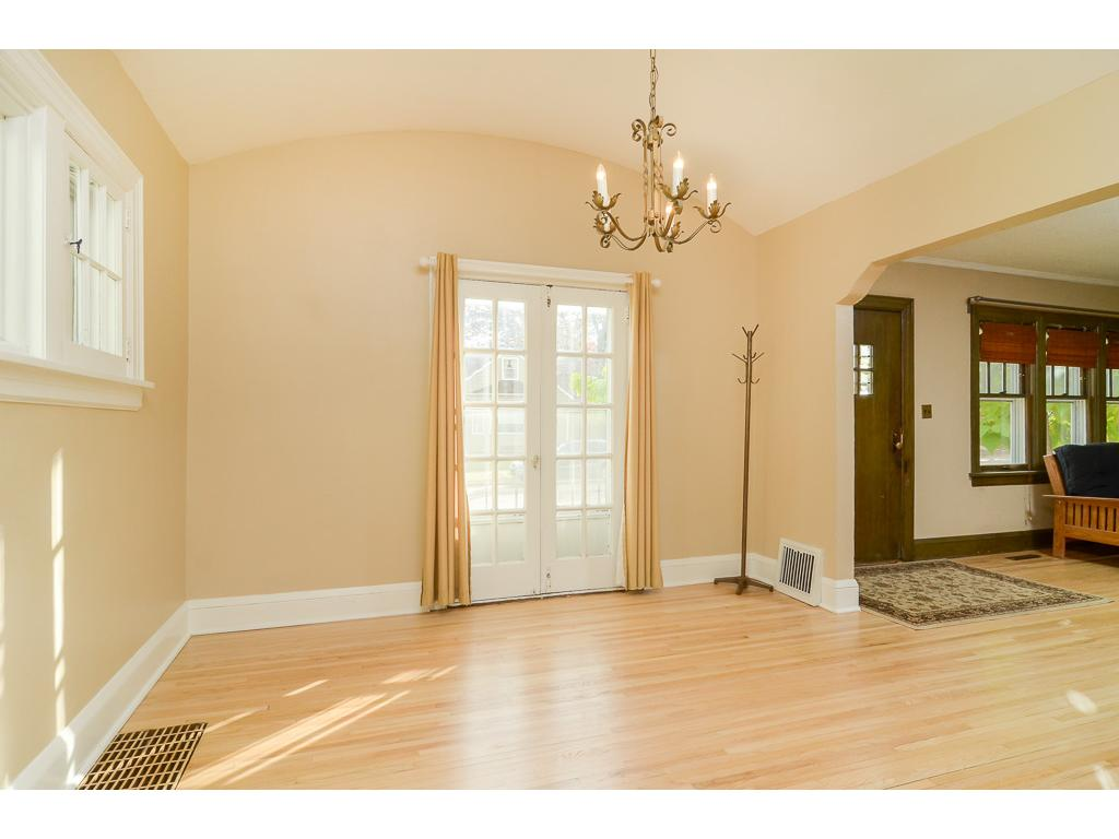 The sun filled dining room has an arched ceiling and opens to the living room.
