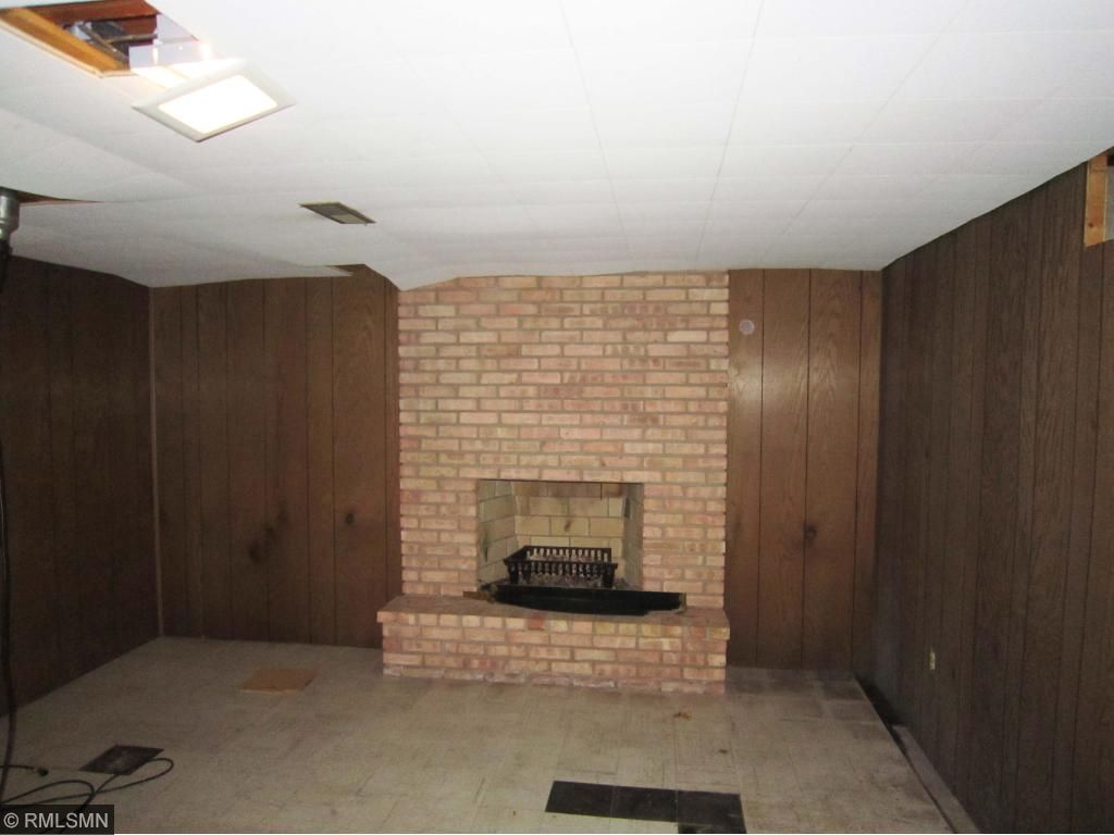 Lower level recroom with another brick fireplace.