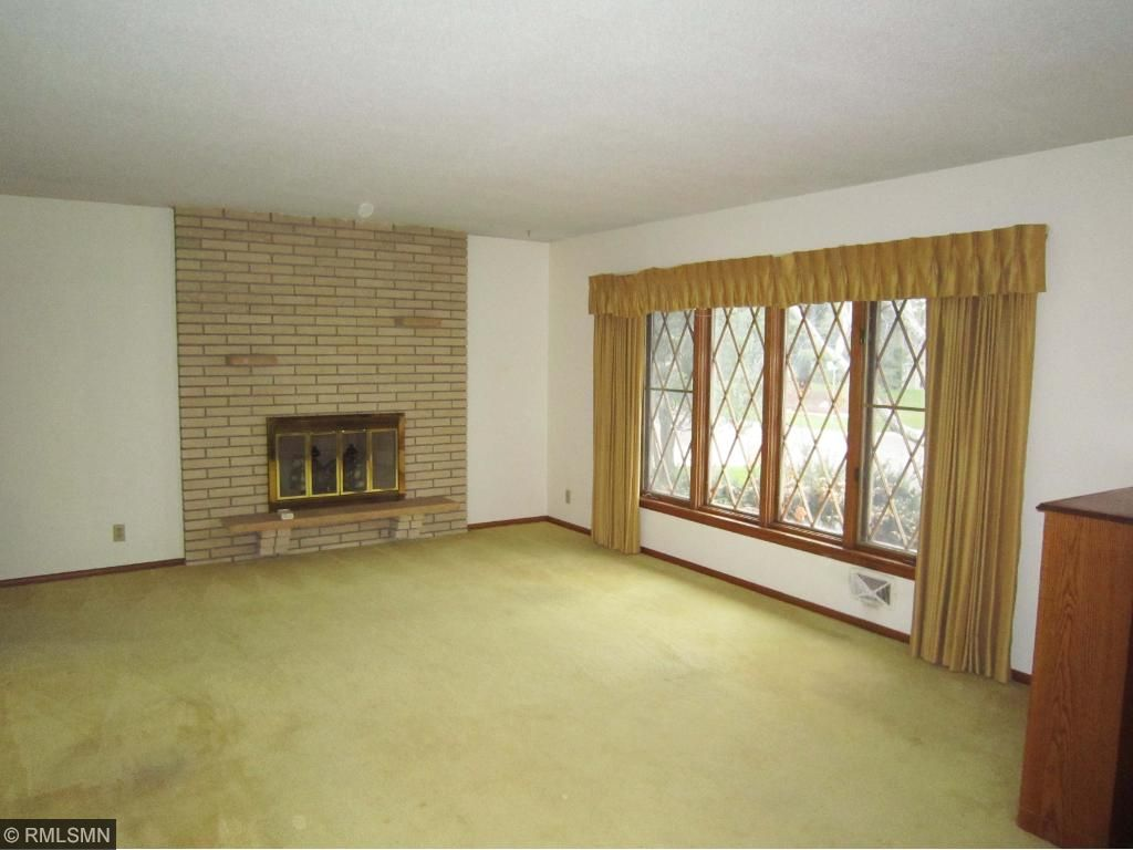 Entertainment sized living room with an attractive brick wood burning fireplace.