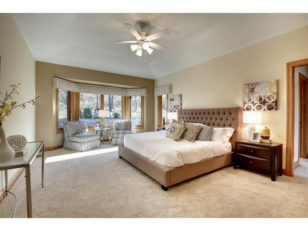 The main floor Owner's Suite is spacious and luxurious, complete with a bay window with lovely wooded views, a tray ceiling, and a walk-in closet.