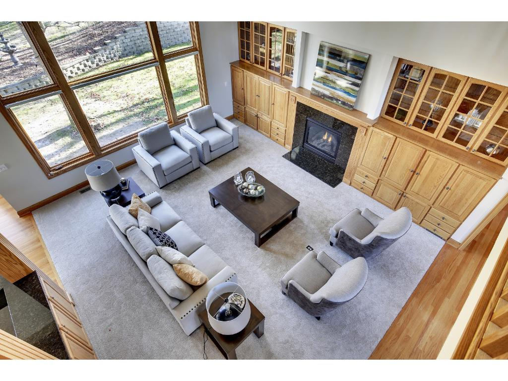 Two story windows in the Great Room let in the sunshine and take advantage of the peaceful wooded views in all seasons.