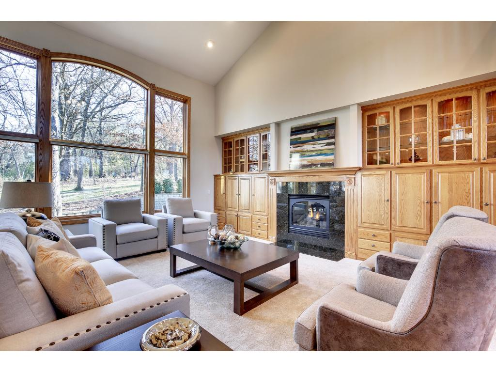 Note the wall of built-ins with lighted cabinetry and a gas fireplace, plus wonderful windows overlooking the lush back yard.