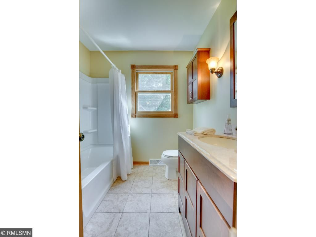 Updated full bath with ceramic tile floors, and new cabinets also features a linen closet just outside the door.