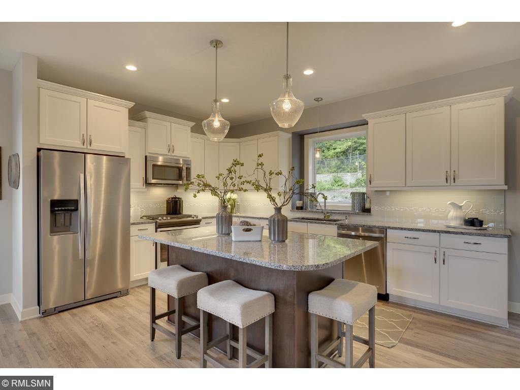 Visit on-site to tour the model and this kitchen featuring a large center island, granite counters, and stainless appliances. Visit on-site to tour the model. Pleasant Ridge. Summit Hill., St. Paul.