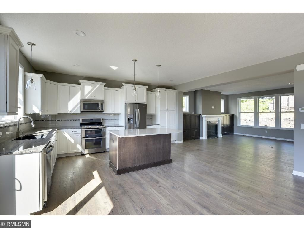 Visit on-site to tour the model and this kitchen featuring a large center island, granite counters, and stainless appliances. Pleasant Ridge. Summit Hill., St. Paul.