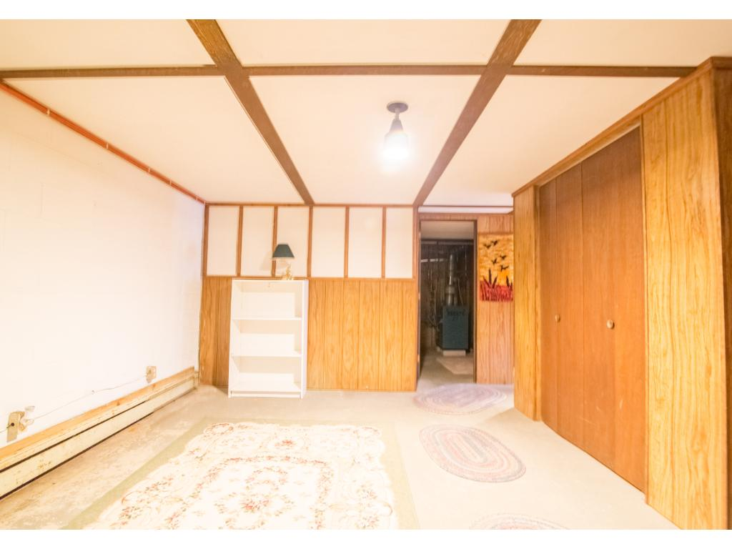 Open room in the basement at bottom of stairs, could use flooring and updates