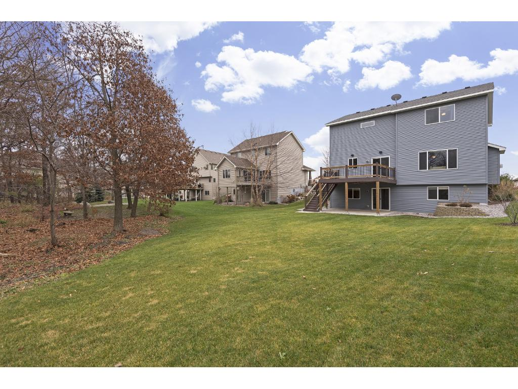 Large deck overlooks level 1/3 acre lot bordered by woods.