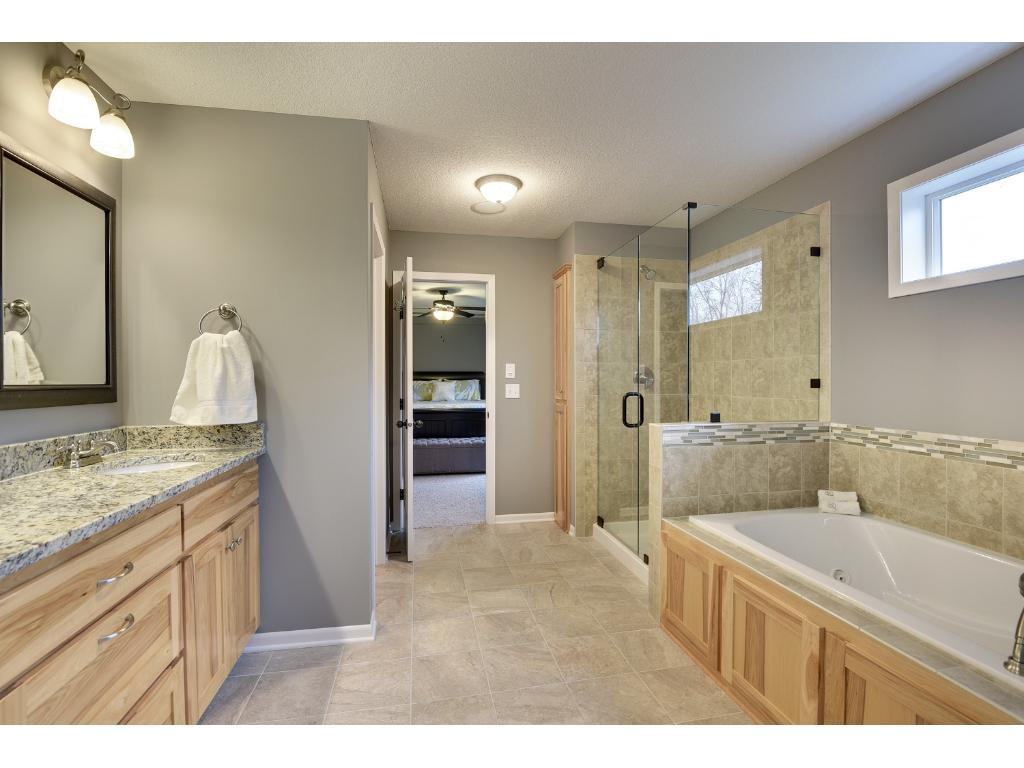 Bathroom has a double sink with built-in vanity and a desired soaker tub.