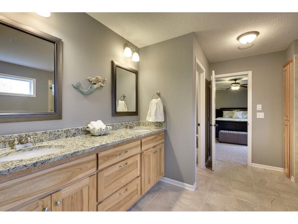Gorgeous stone/tile bathroom with separate walk-in stone shower and seamless glass enclosure.