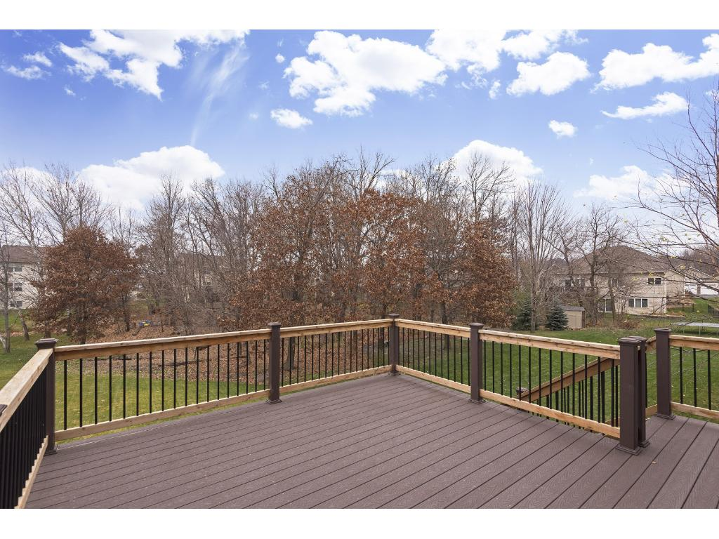 Maintenance-free 16' x 16' deck with wooden and metal railings overlooking a level, grassy and wooded back yard.