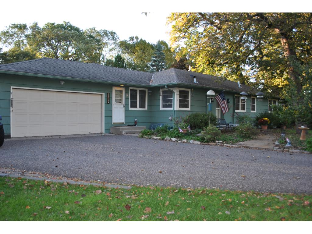 Two car attached garage with additional paved parking to the side.