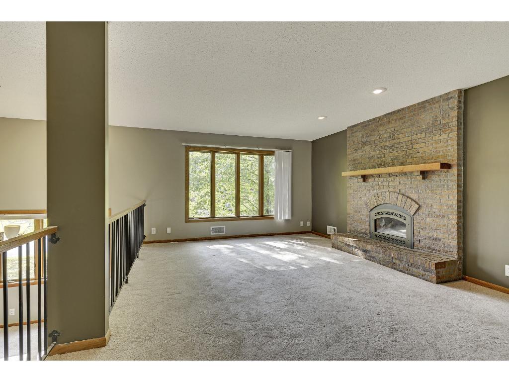 Living room fireplace has newer gas fireplace insert; door access to deck and backyard.