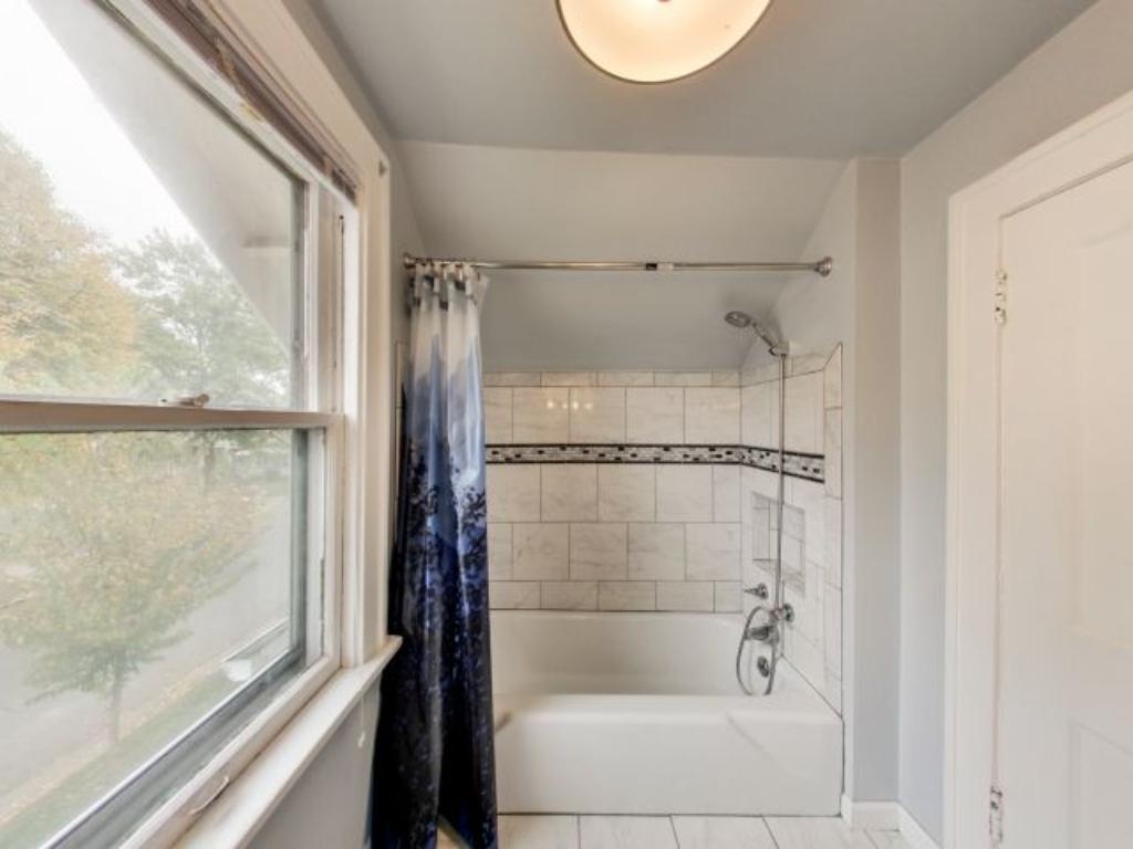 Renovated and updated upper level bathroom featuring tiled shower and new tile flooring.