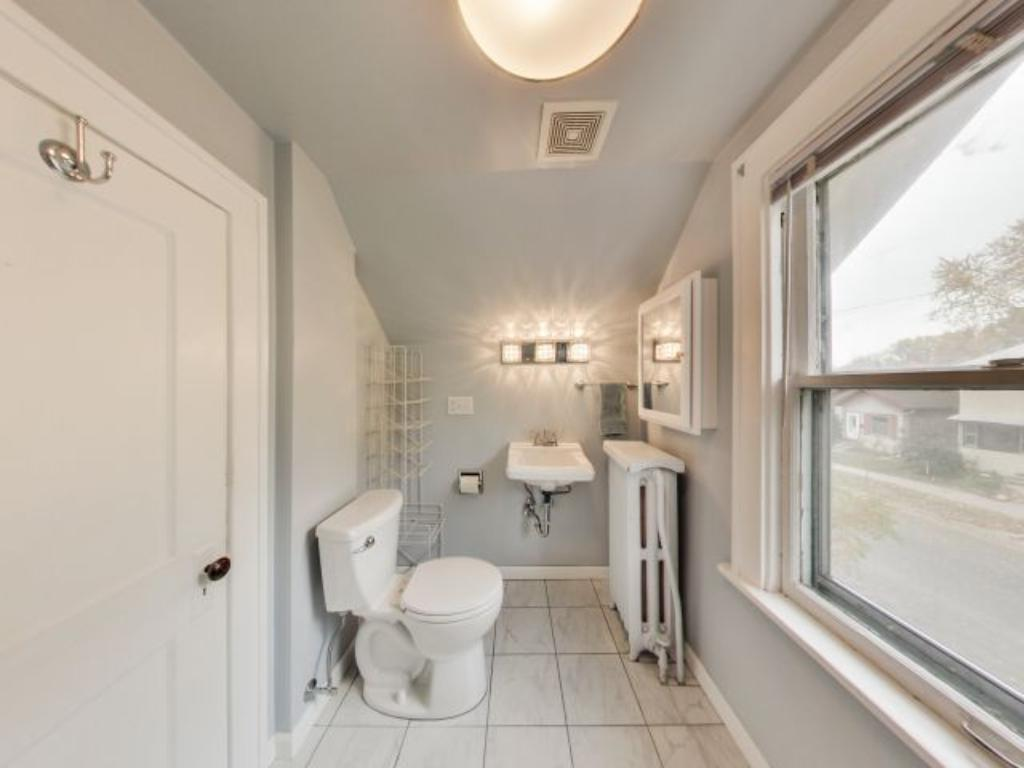 The updated bathroom shines with clean white tiled floor and tiled shower.