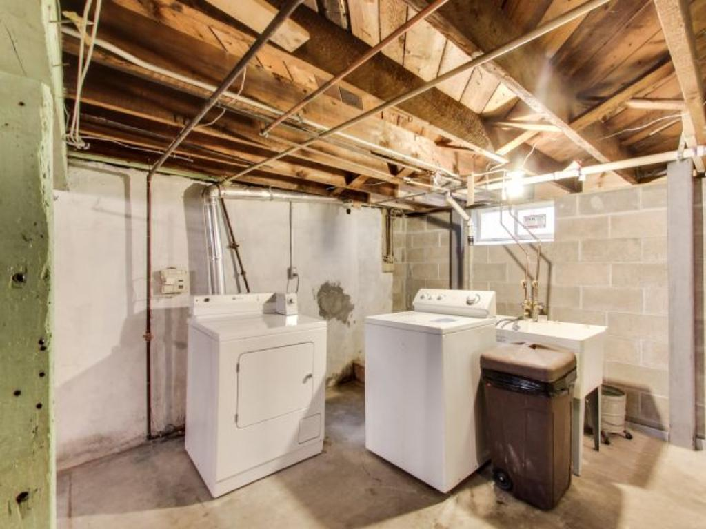 Washer and dryer conveniently located right at the base of the basement stairs. Basement offers spacious ceiling height for older home and plenty of storage space.
