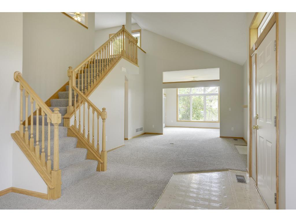 Wide stairway to family room, open floor plan with vaulted ceilings.
