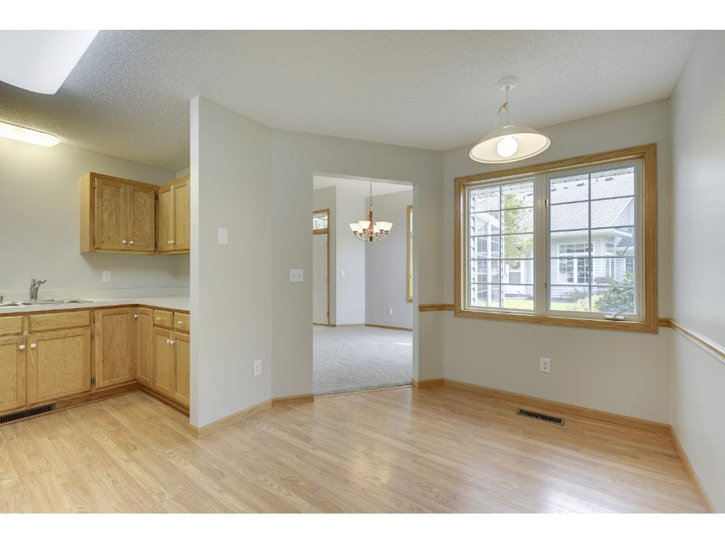 Breakfast area and kitchen feature wood floors and large windows.