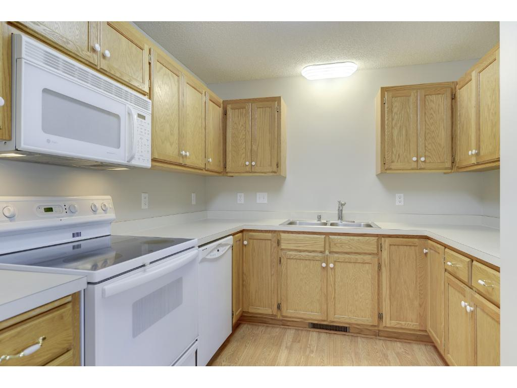 Kitchen features lots of cabinets, ample prep space and wood floors.