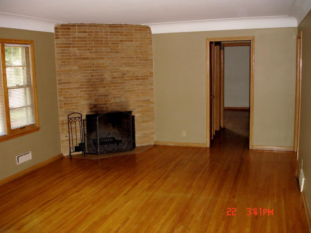 Main level living room has hardwood floors and a fireplace.