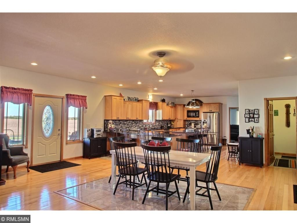Stunning kitchen/dining room with open floor plan. Hardwood flooring with tile under the dining table and center island.