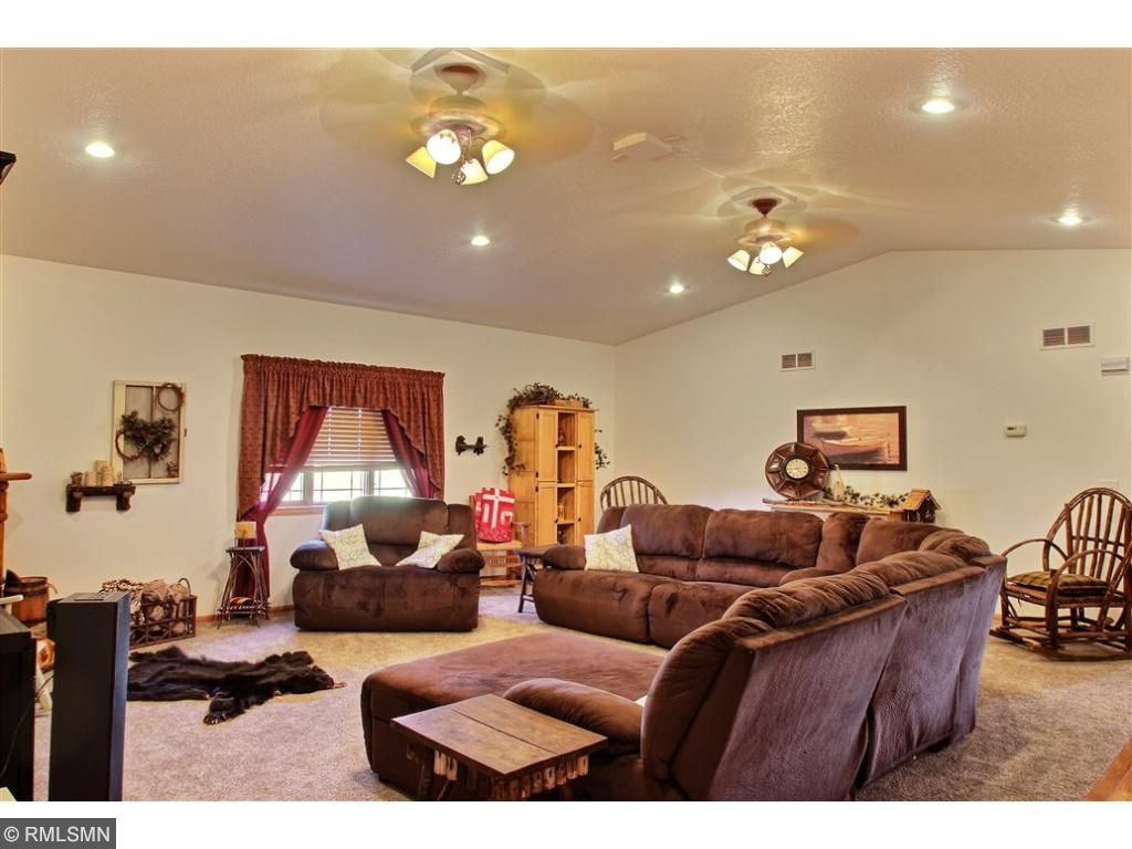 Family room features vaulted ceiling, two fans, a electric fireplace along with room for the entire family.