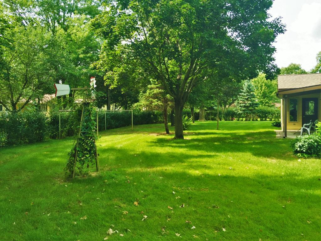 Half Acre lot with mature trees and many flower beds