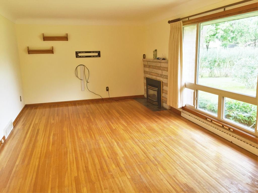 Giant living room with all hardwood flooring and Gas fireplace and large vinyl picture window