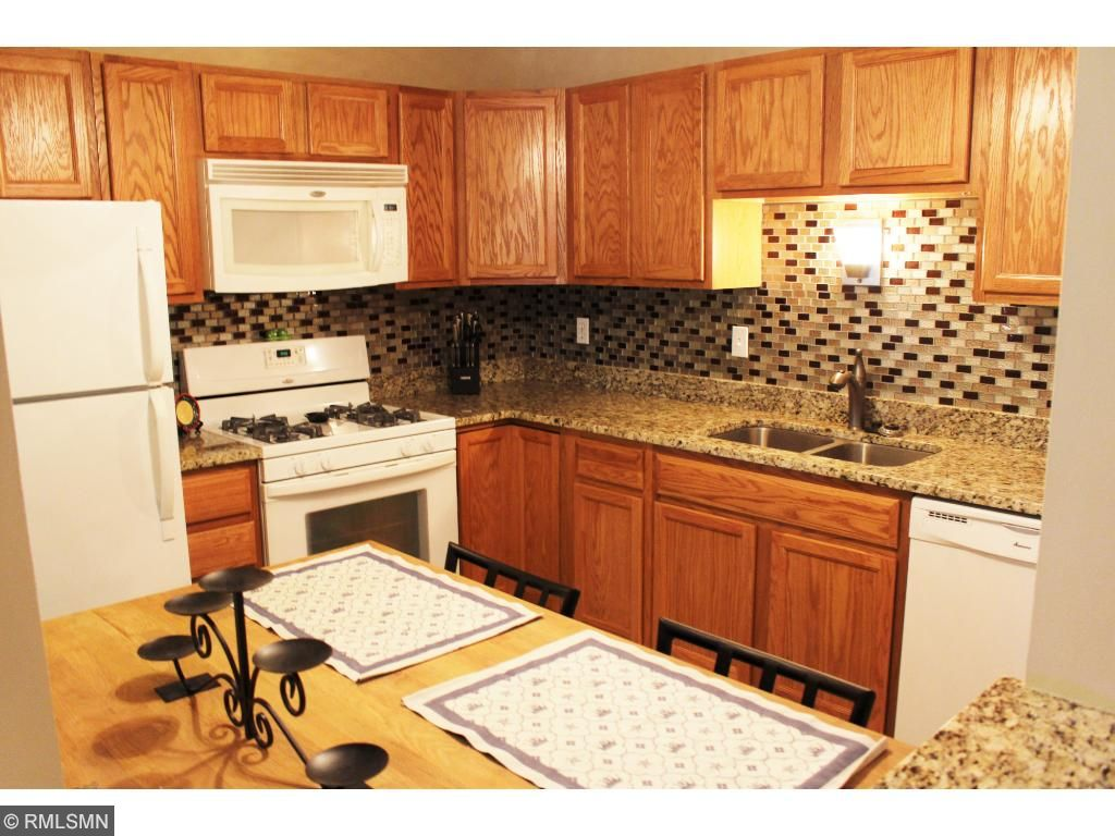 Gorgeous kitchen with granite counters and glass backsplash and gourmet gas stove.