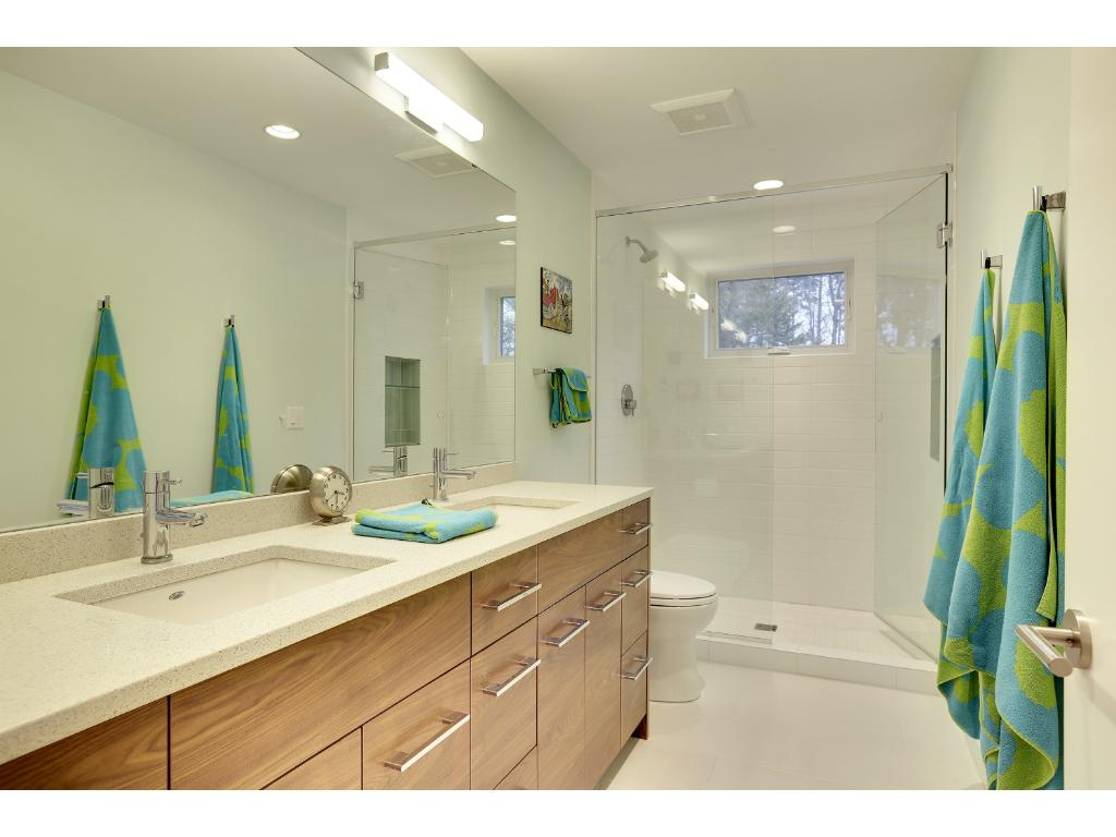 Luxurious master bathroom with the finest amenities - heated tile floor, Carrara marble countertop, gorgeous white basin sink, dual wall-mounted polished chrome faucets, glass shower with tiled walls and floor, as well as an elegant soaking tub!