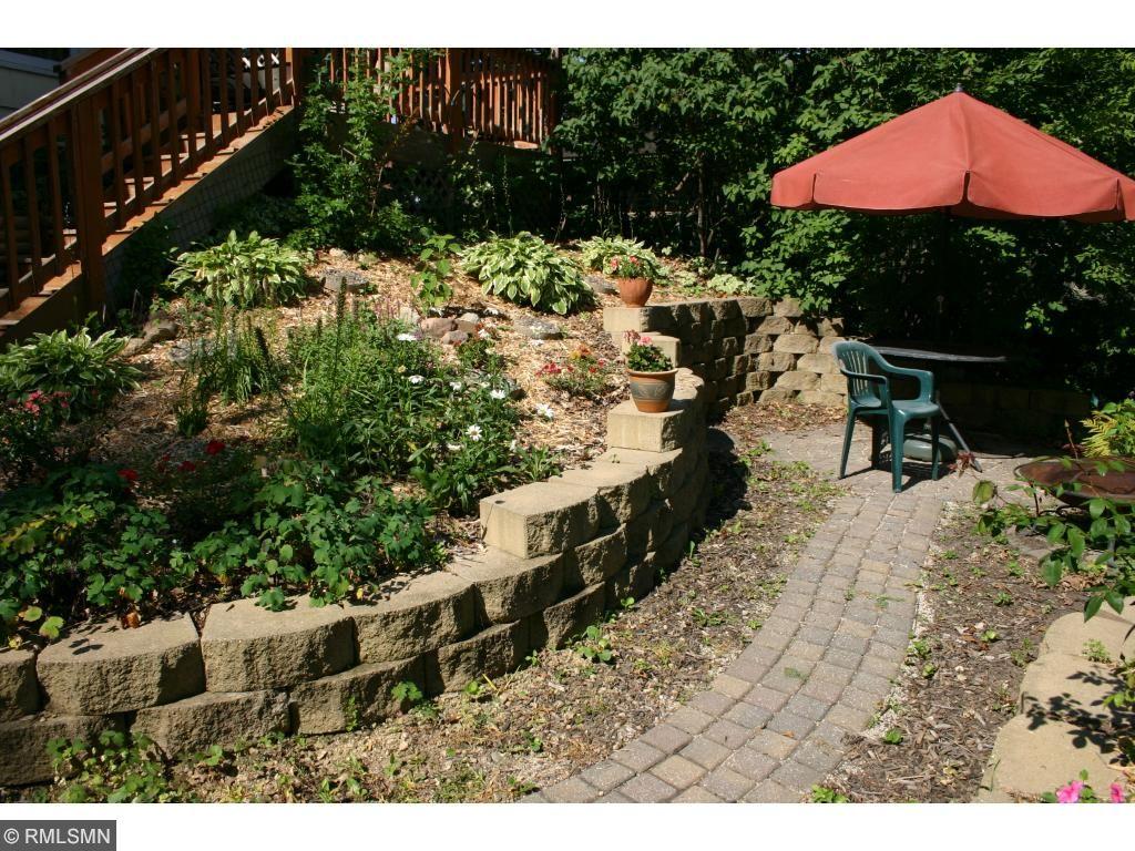 A cobblestone patio is next to garden terrace.