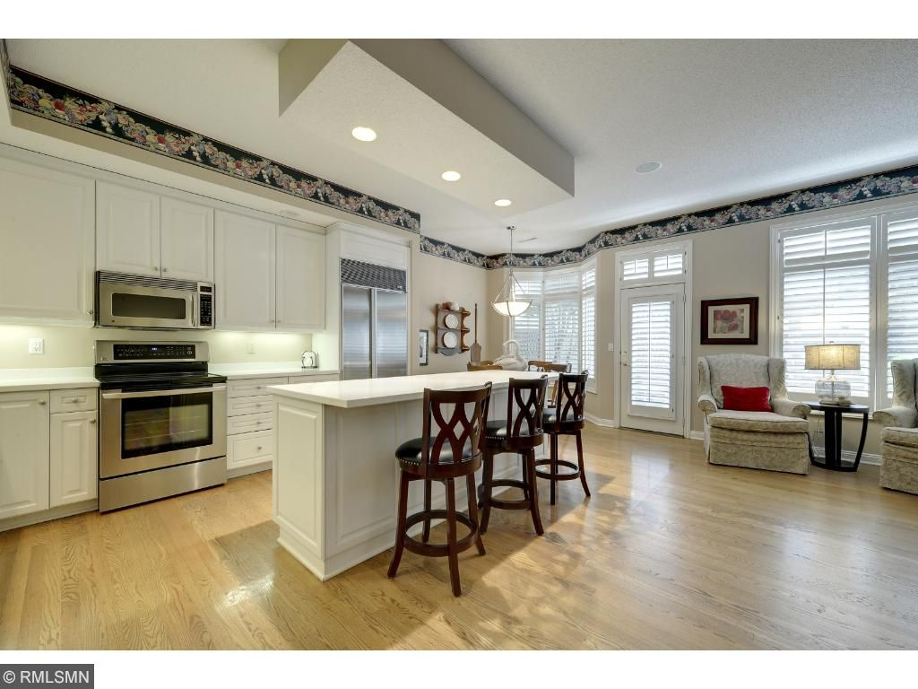 Large kitchen, open to the family room. Stainless steel appliances, white cabinetry and counters.