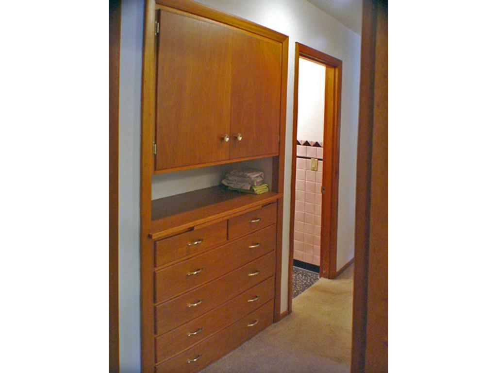 Built in located in hallway, beautiful wood and very functional. Pull out board for folding clothes.