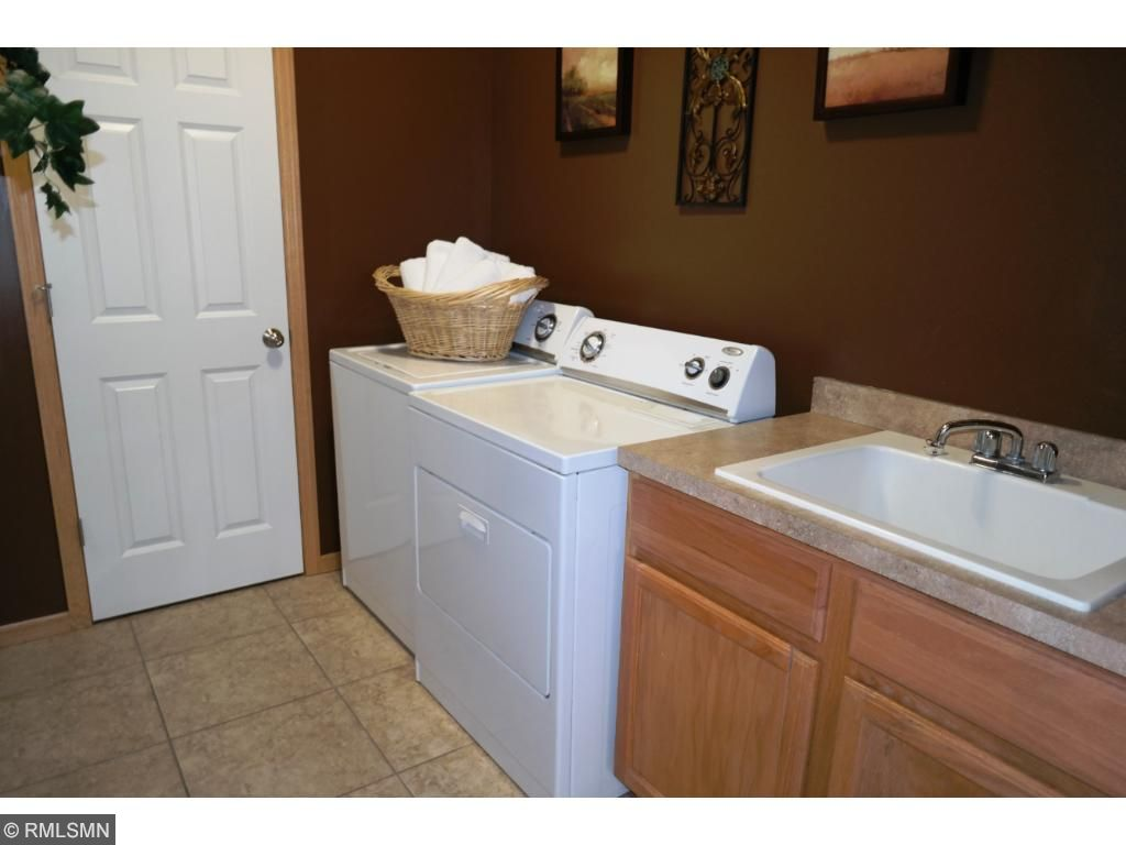 Main level laundry with wash sink and coat closet.