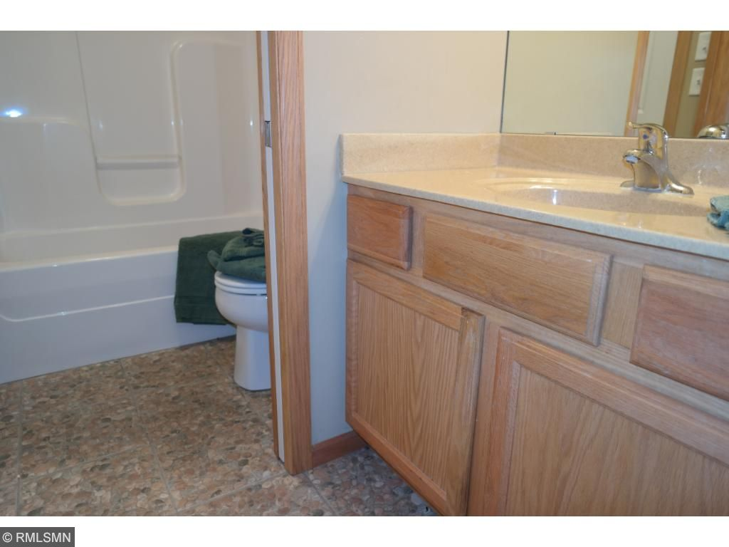 This bathroom with a stone floor also has a separate sink and bath area. The bedroom also shares this bathroom along with the family room. Don't forget the 500+ square foot storage area/mechanical room!!!! Storage galore!! This home is a 10+ +