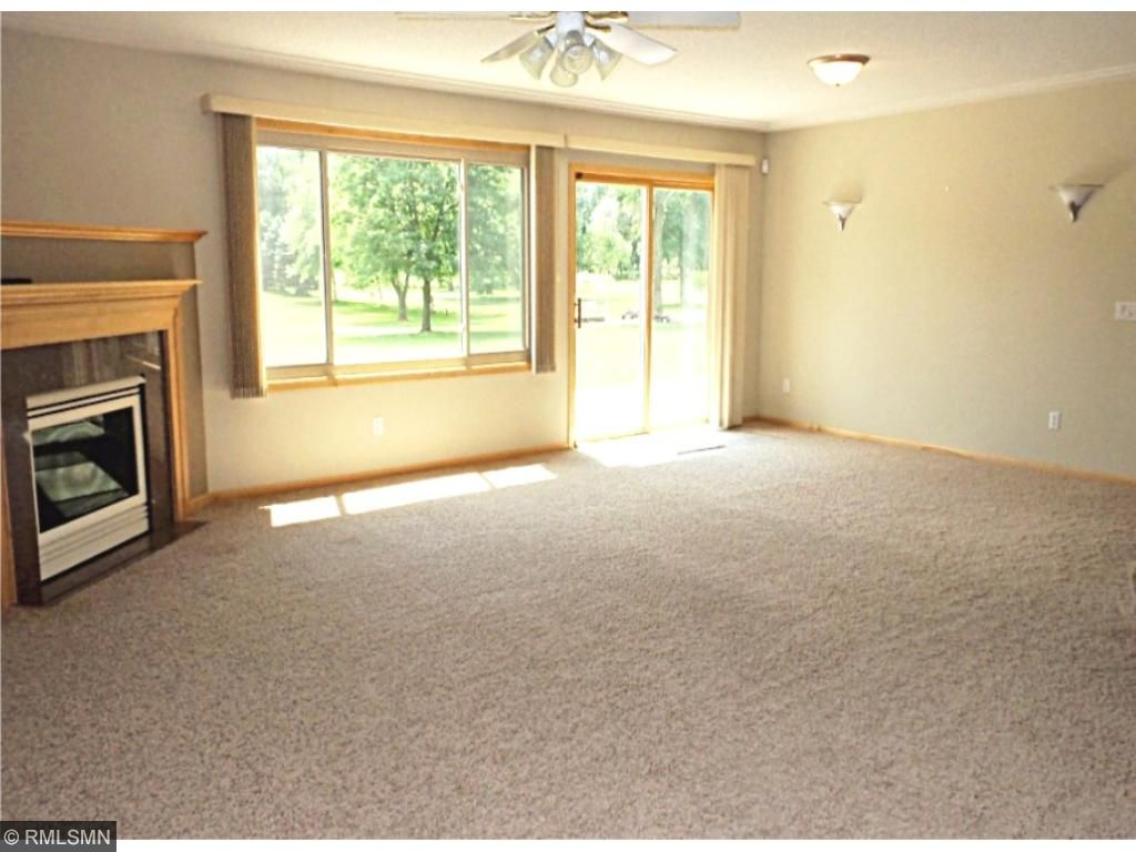 "Lower Level ""amusement"" room with wet bar, gas fireplace and sliding glass door that leads to the patio.  Ample lighting which includes a ceiling fan and sconces."